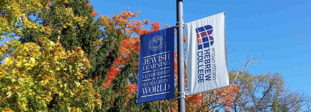 Two flags, Hebrew College's name and logo.  Fall leaves in the background.
