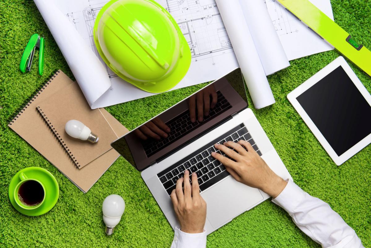 computador ao centro em cima de fundo verde, com tablet, capacete de engenheiro e café ao lado.